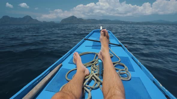 Travel Holiday. Man Legs on Banca Boat Deck on Island Hopping Trip Approaching Tropical Island