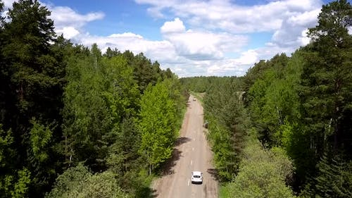 Vehicle Drives on Gray Destructed Road Between Green Forests