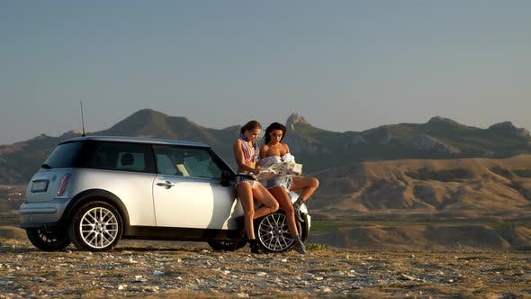 Two Young Women Watch the Road Map Standing Near the Car in Backdrop of Mountain Range at the Sunset