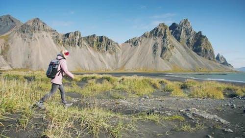 Morning Scene of Female Traveler Exploring Stokksnes Cape with Vestrahorn (Batman Mountain) on