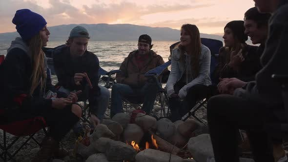 Thumbnail for Gruppe von Millenials versammelte sich um das Lagerfeuer bei Sonnenuntergang