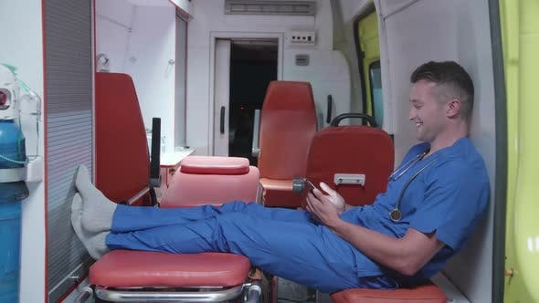 Thumbnail for Man Sit with Phone in Ambulance Car, Watch Something and Smile.