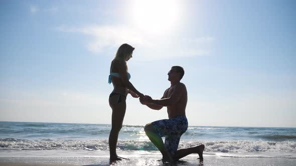 Thumbnail for Young Man Stand on Knee and Marriage Proposal To His Girlfriend Summer Vacation. Happy Pair Hugging