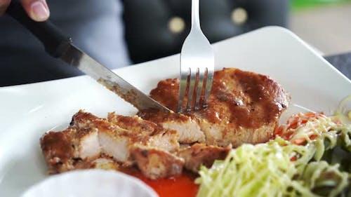 Close up of hand cutting a pork steak