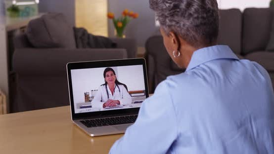Mature African woman talking to doctor on laptop