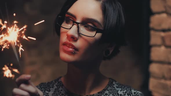 Thumbnail for Portrait of Young Goth Woman with Short Black Hair, Wearing Glasses. He Looks at a Burning Sparkler