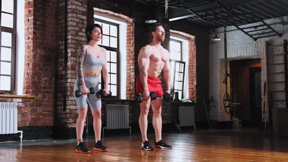 Couple in the Gym  Holding Dumbbells and Leaning Down  Hands Training