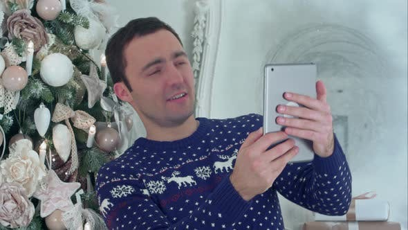 Thumbnail for Young Handsome Man in a Christmas Knitted Sweater Taking Selfies on a Tablet