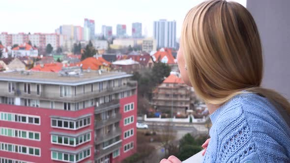 Thumbnail for A Young Beautiful Woman Stands on a Balcony and Looks Around with a Mellow Smile - Closeup
