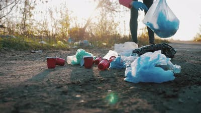 Care About Nature. Volunteer Girl Collects Trash in the Trash Bag. Trash-free Planet Concept. Nature