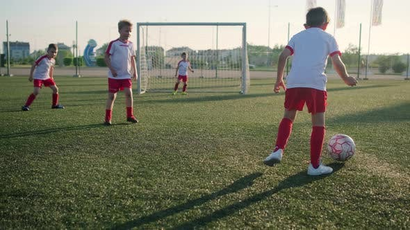 Group of Little Football Players Is Playing Soccer Scoring Goal