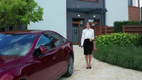 Thumbnail for Woman Walking on Courtyard Path and Getting in Car