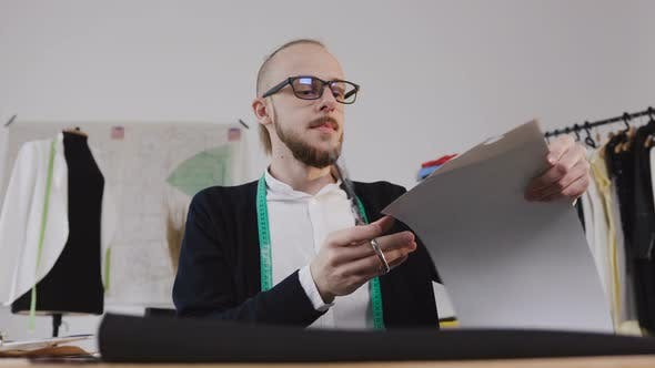 Cover Image for Young Beared Designer or Tailor in Eyeglasses who Sitting at a Workplase at the Studio