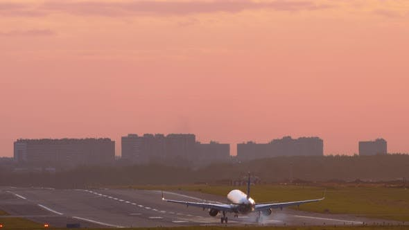 Rear View of a Plane Landing at Sunset