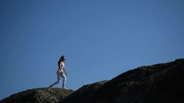 Das Mädchen macht ein Training am Rande der Klippe, Springen und Ausfallschritte.